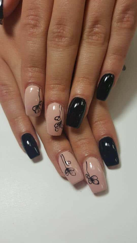 black nails and beige nails with black floral design.