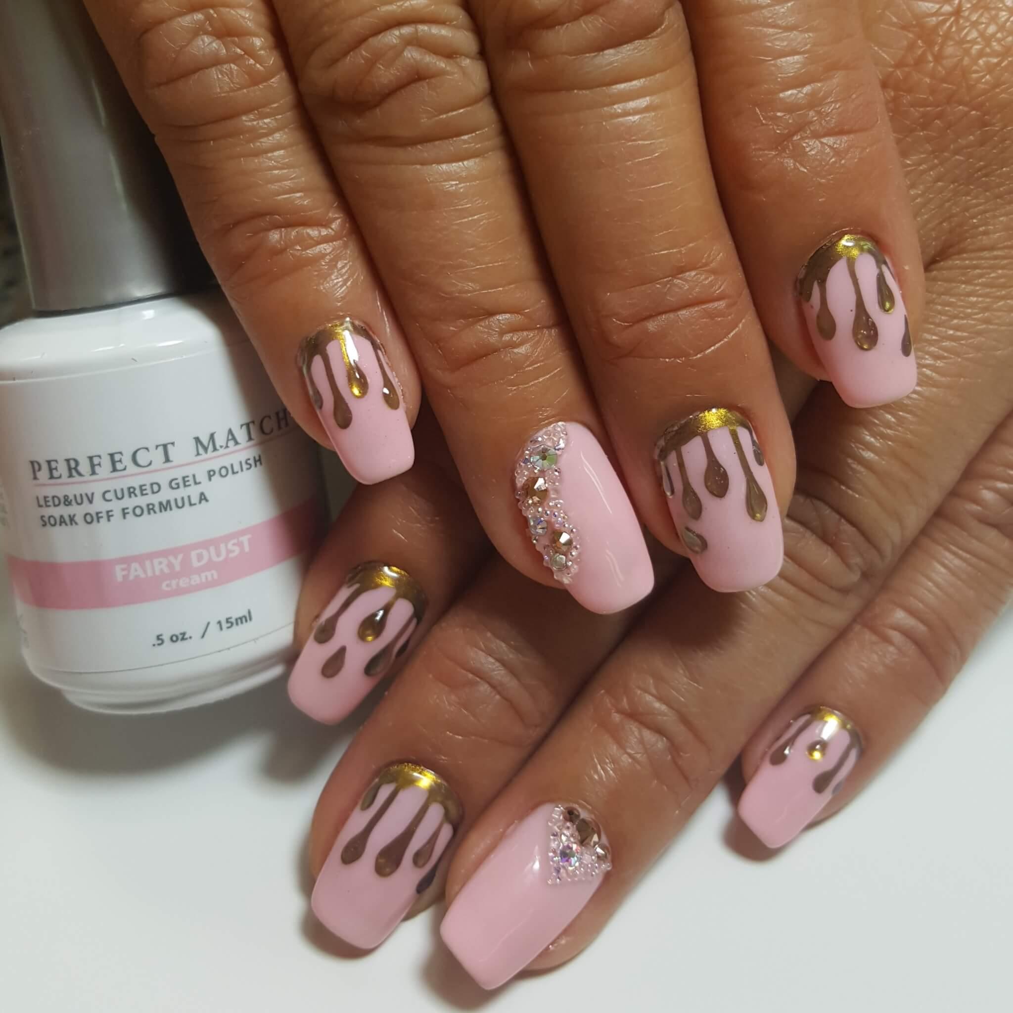 set of pink nails with golden details.