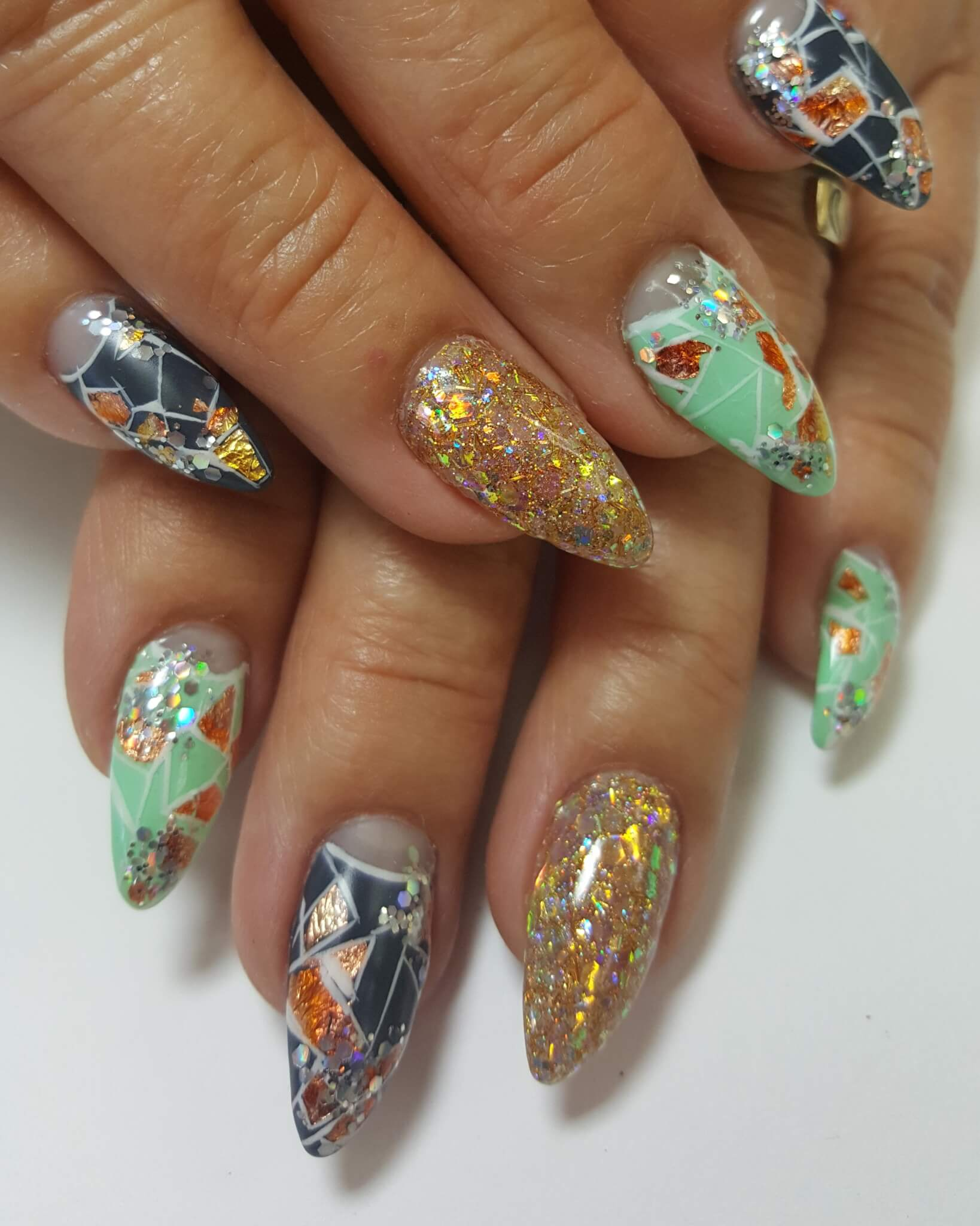 intricate gold, green and black nails with flaky patterns.