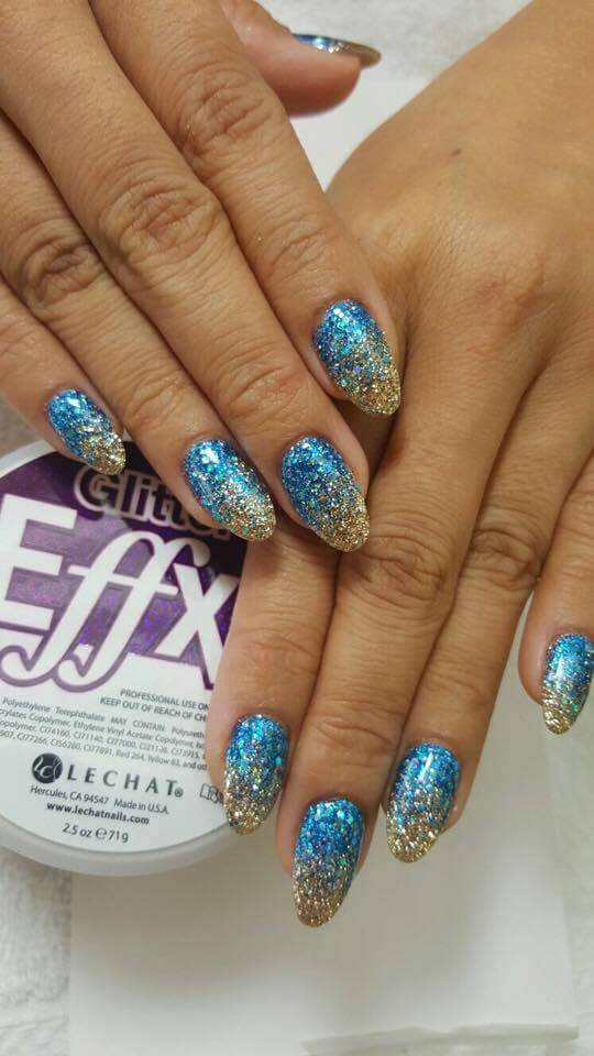 set of blue and gold sparkly nails.