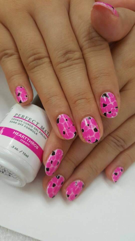 set of pink nails with black accents.