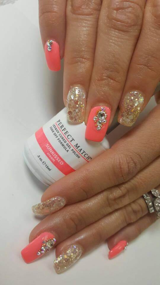 couple of hands holding a bottle of Perfect Match Sunkissed, nails painted such color and decorated with gemstones.
