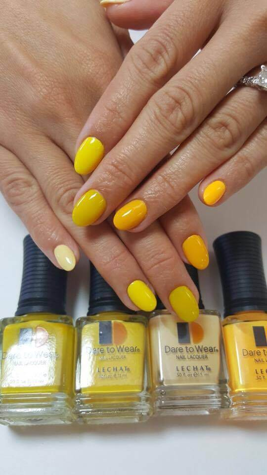 couple of hands with yellow nails of different shades, various yellow Dare to Wear bottles aligned under them.