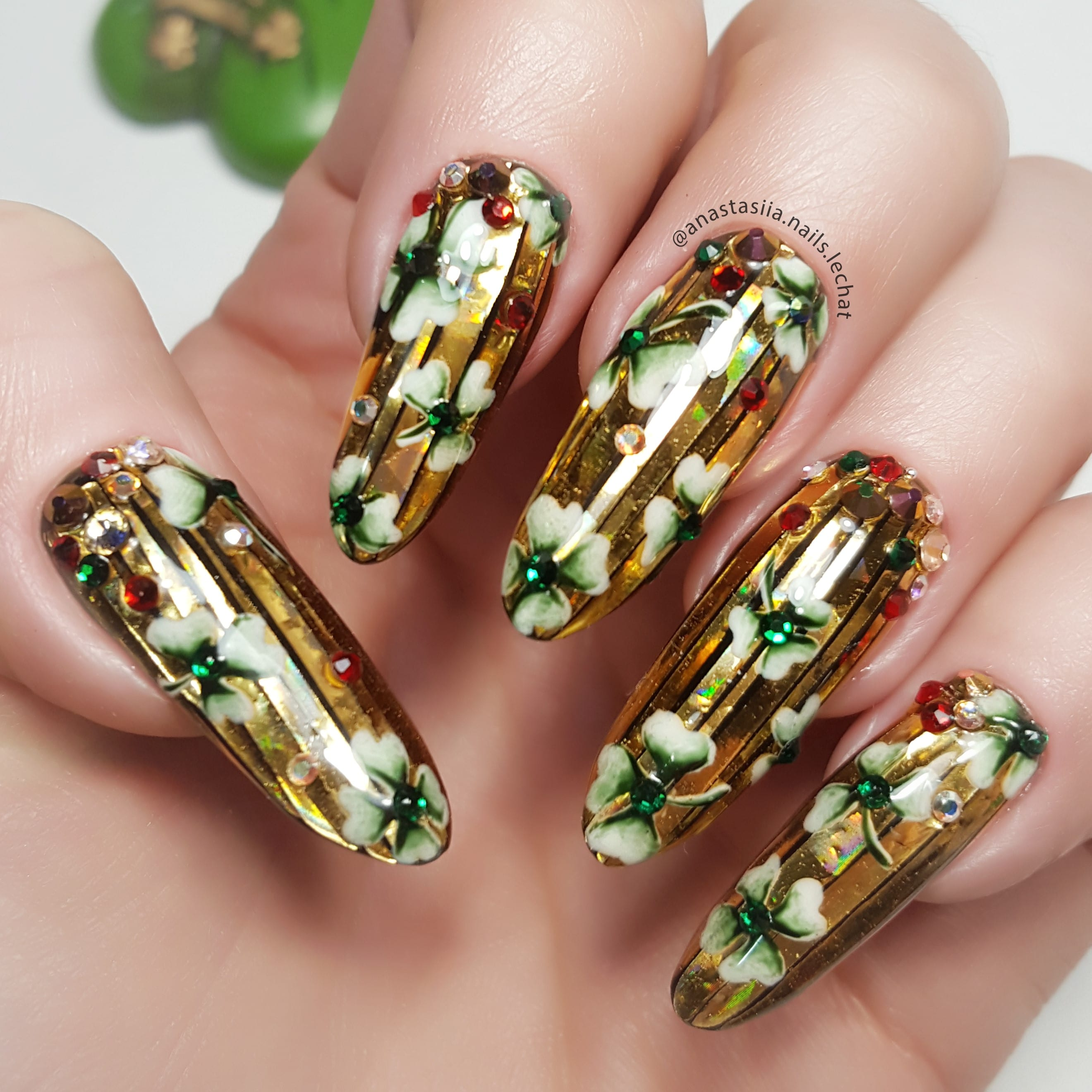 Nail art with golden paint and green flowers