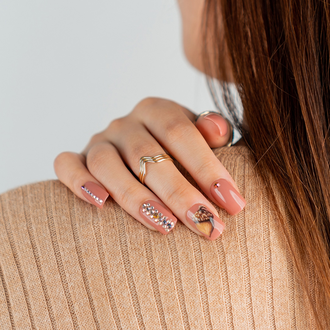 nail art with acorn design and soft brown colors