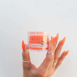 Hand holding dip powder jar with nails in color Orange Infusion.