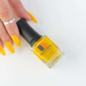 Fingers holding yellow polish in LeChat's Dare to Wear color Sunshine on My Mind