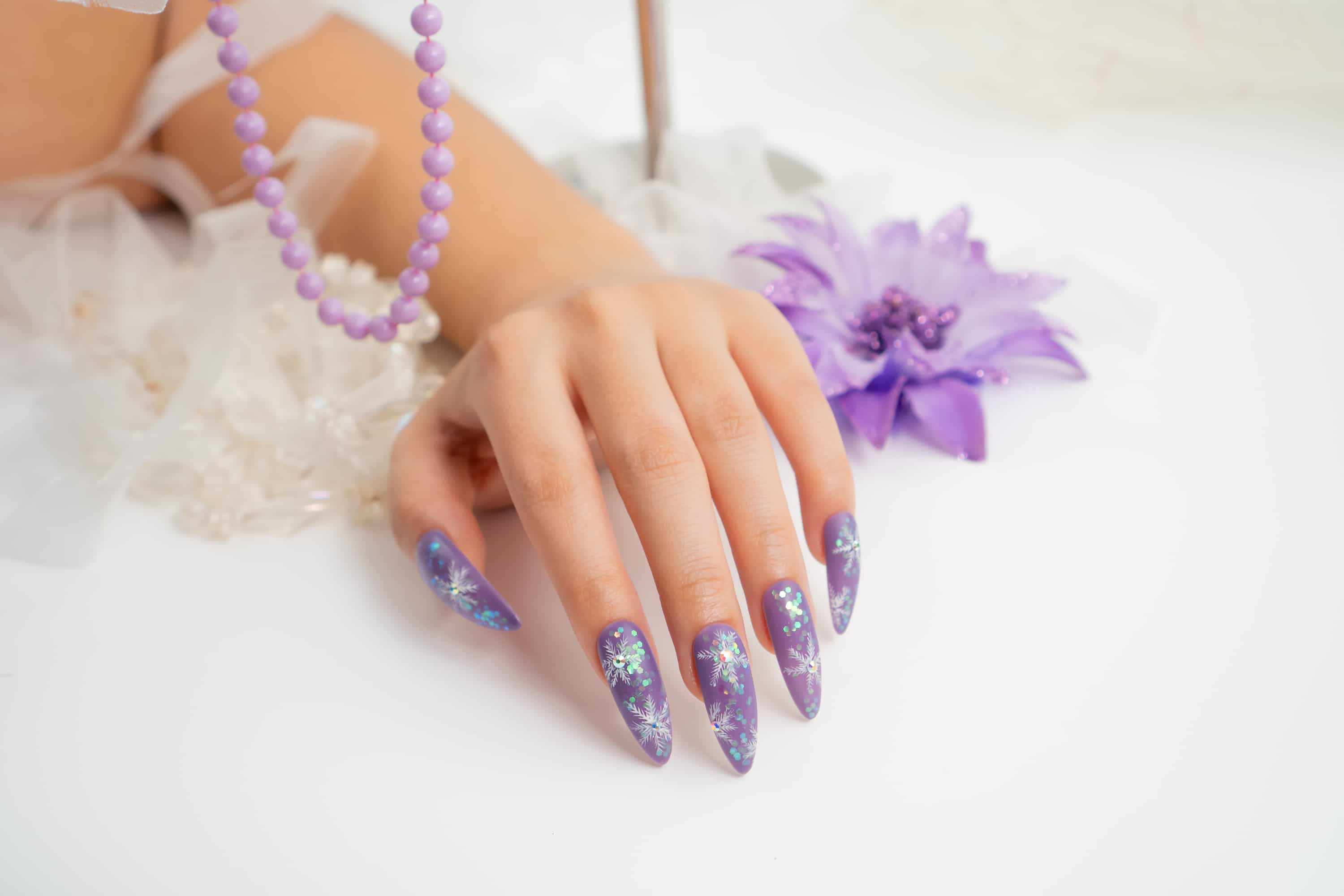 Hand with purple nails and sparkly star designs