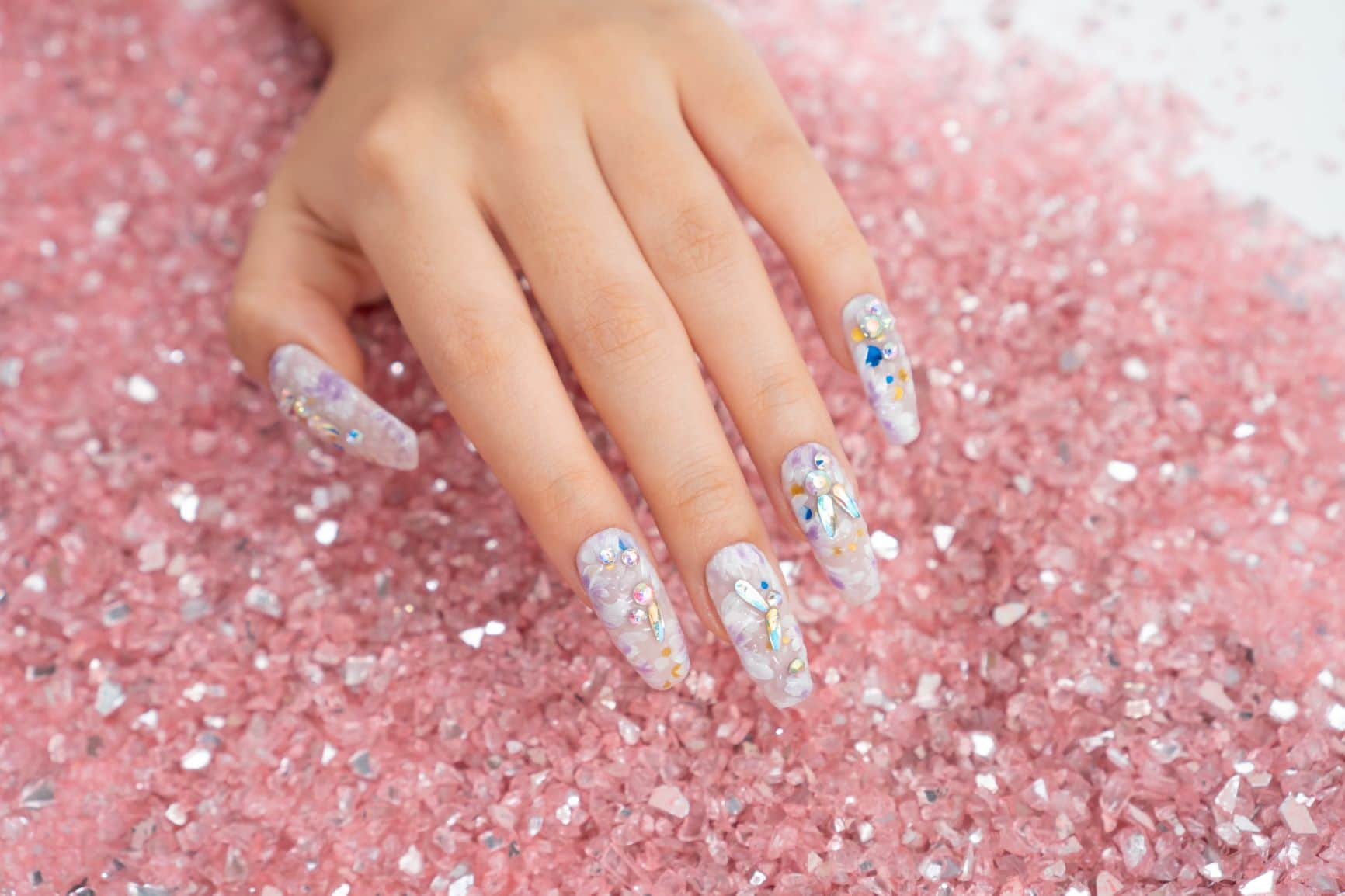 set of white and blue nails with decorations