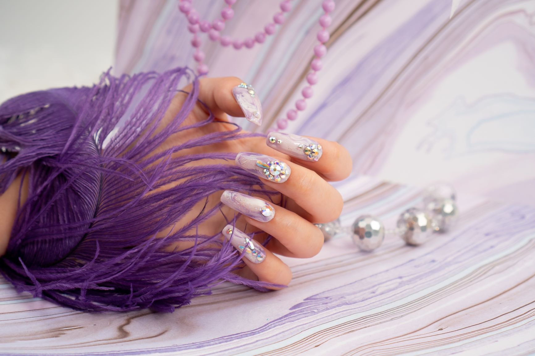 Elegant nails with gemstone decorations and lavender colors