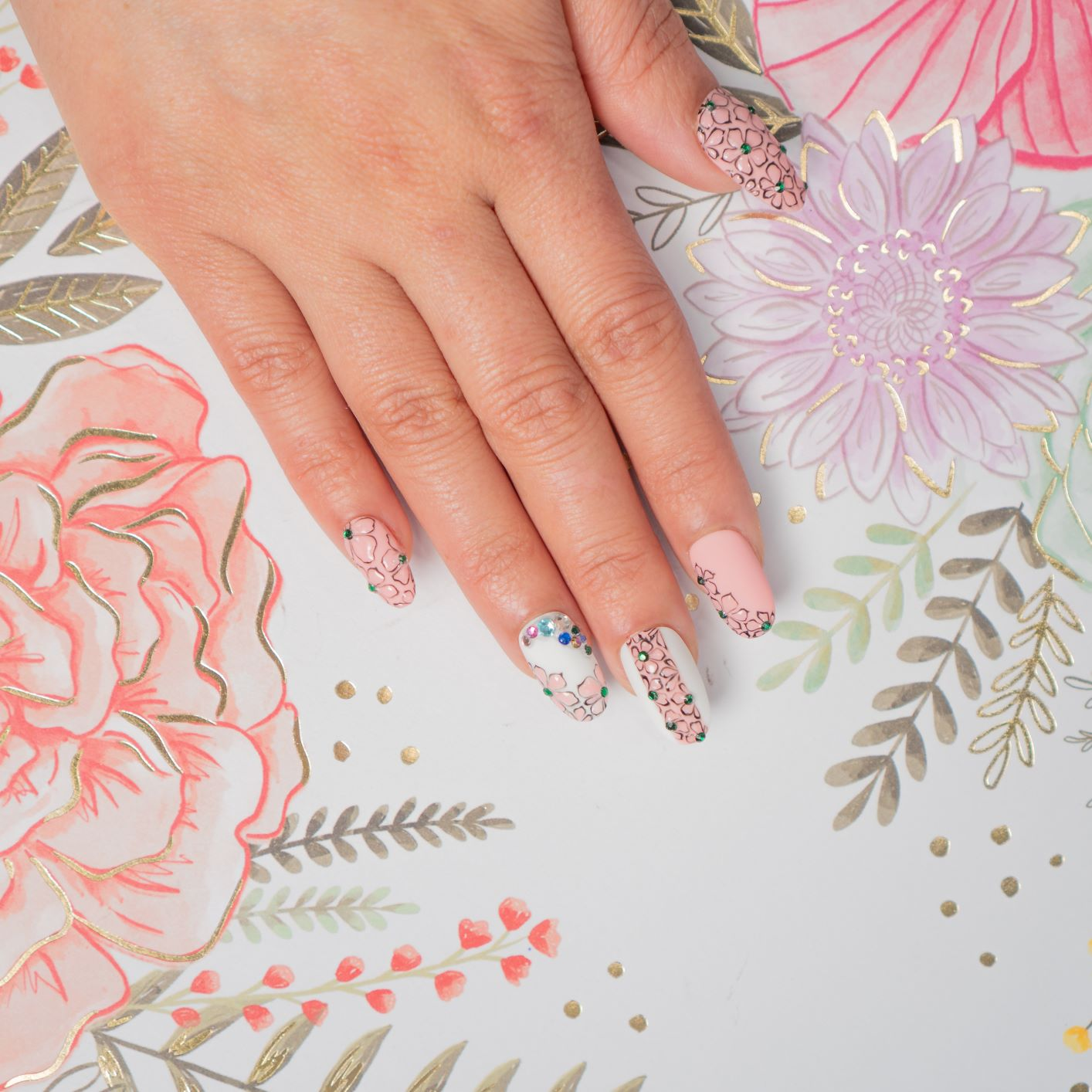 Hand with pink and white nails, decorated with flower patterns and gems