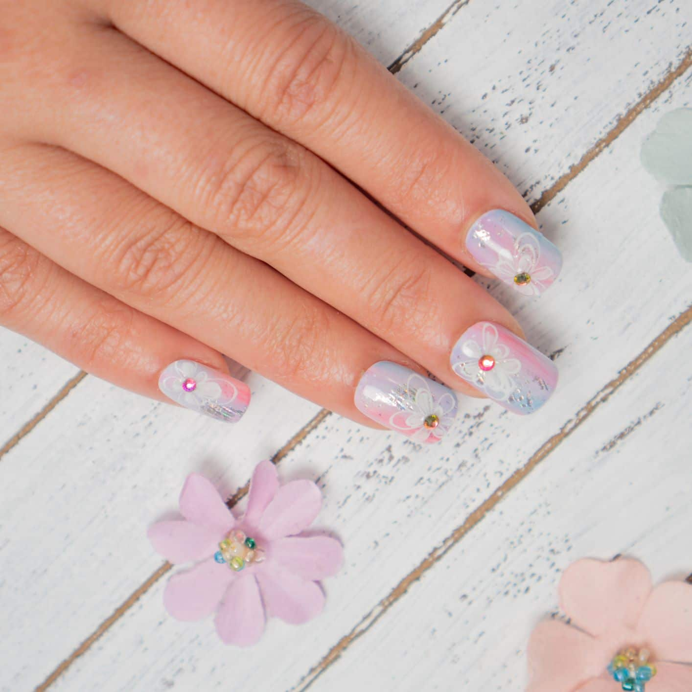 close up of hand with soft colored nails, with flower designs