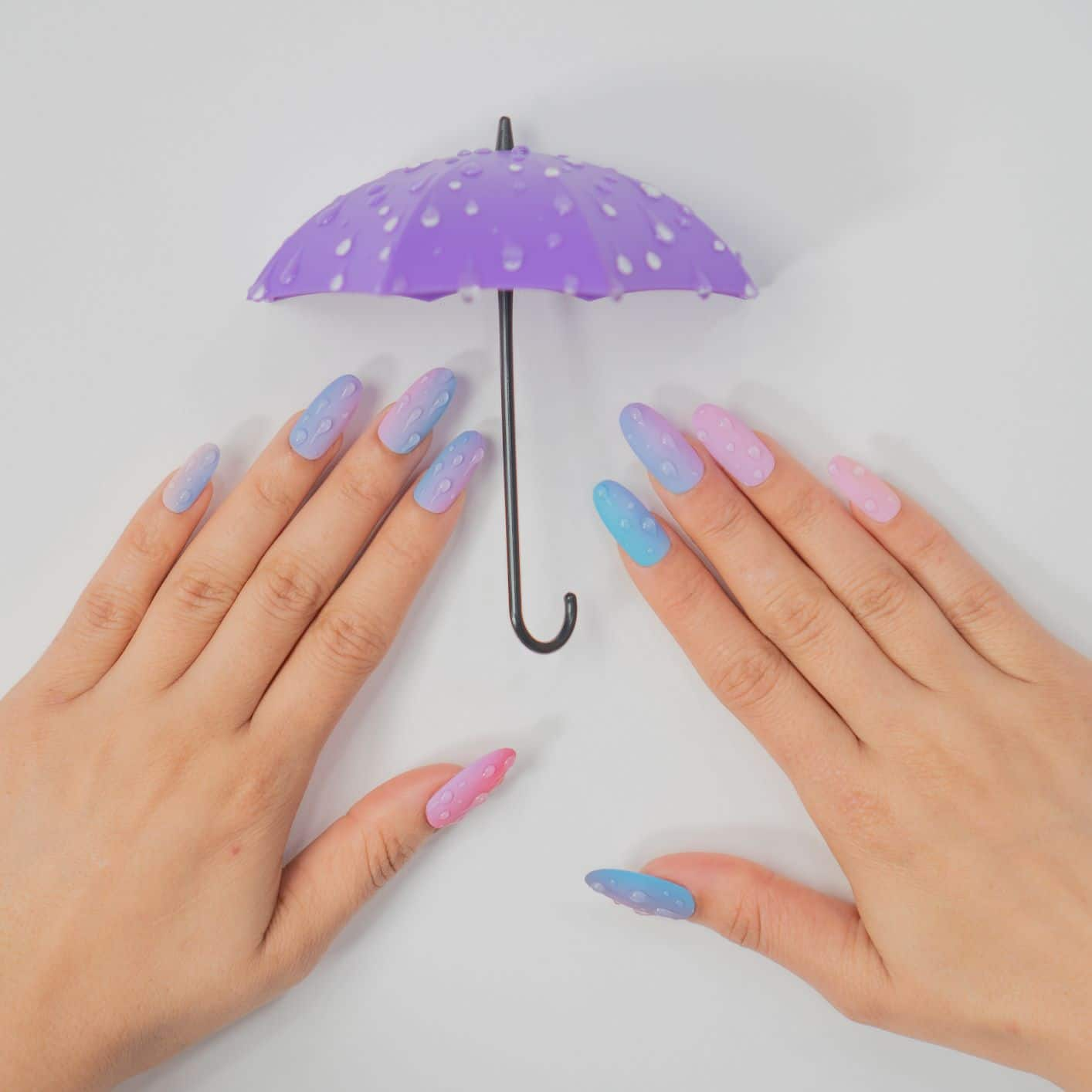 pastel colored nails with raindrop effect decorations