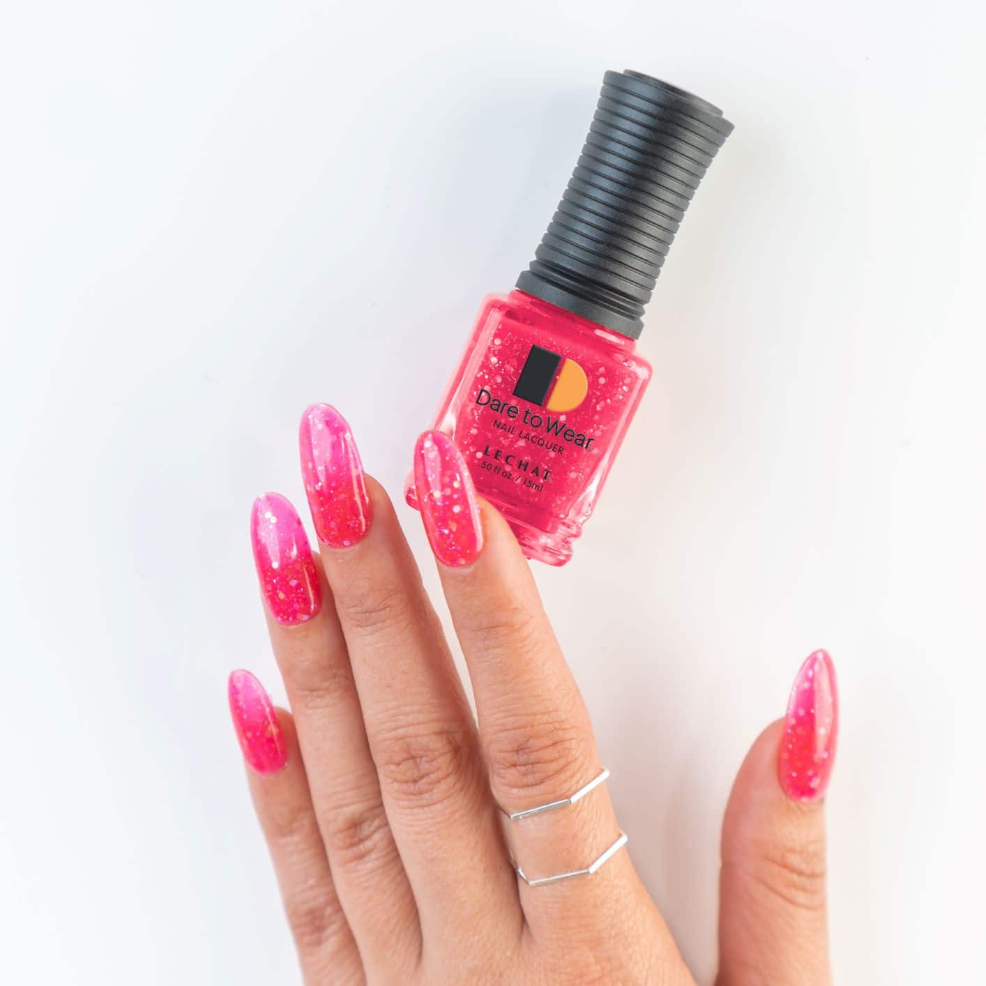 hot pink nails with glitter effect alongside lacquer bottle