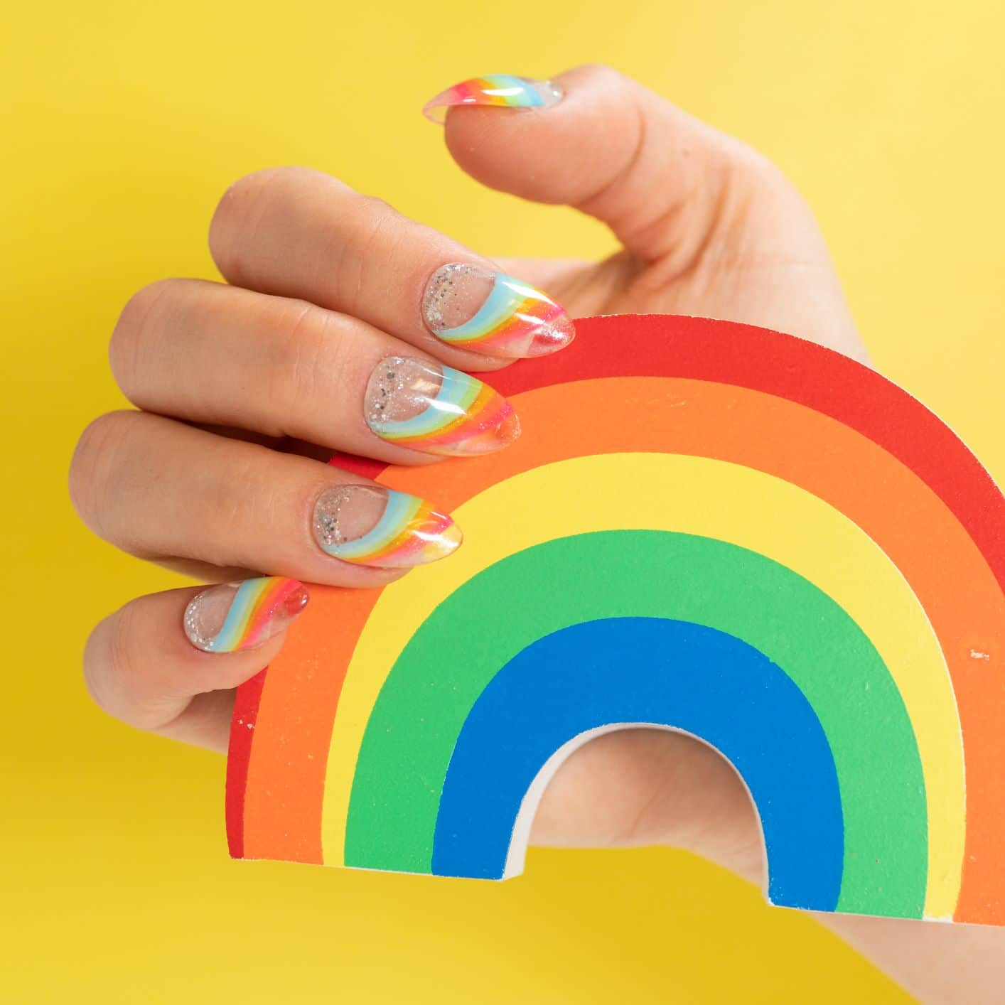 Rainbow-themed art on clear nails