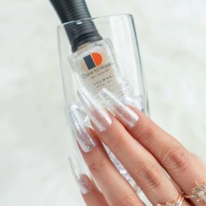 hand holding glass with a bottle of clear and glittery lacquer, nails decorated with it
