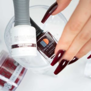hand holding bottle of dark red lacquer and gel, nails decorated with the shade