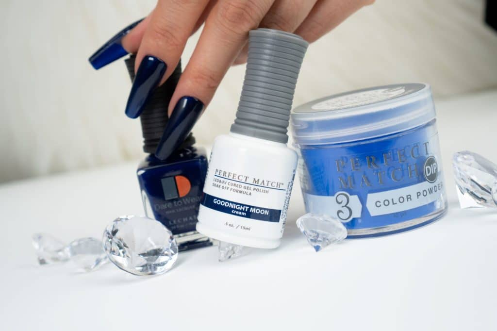 hand holding bottle of blue lacquer and gel, nails decorated with the shade