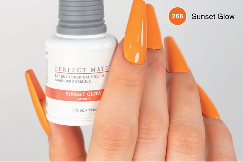 Hand with long orange nails holding a bottle of PM268 Sunset Glow