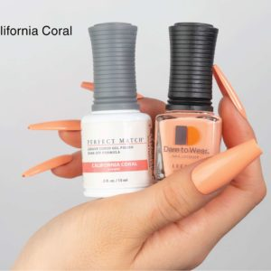 Hand with long beige nails holding DW and PM 269 California Coral