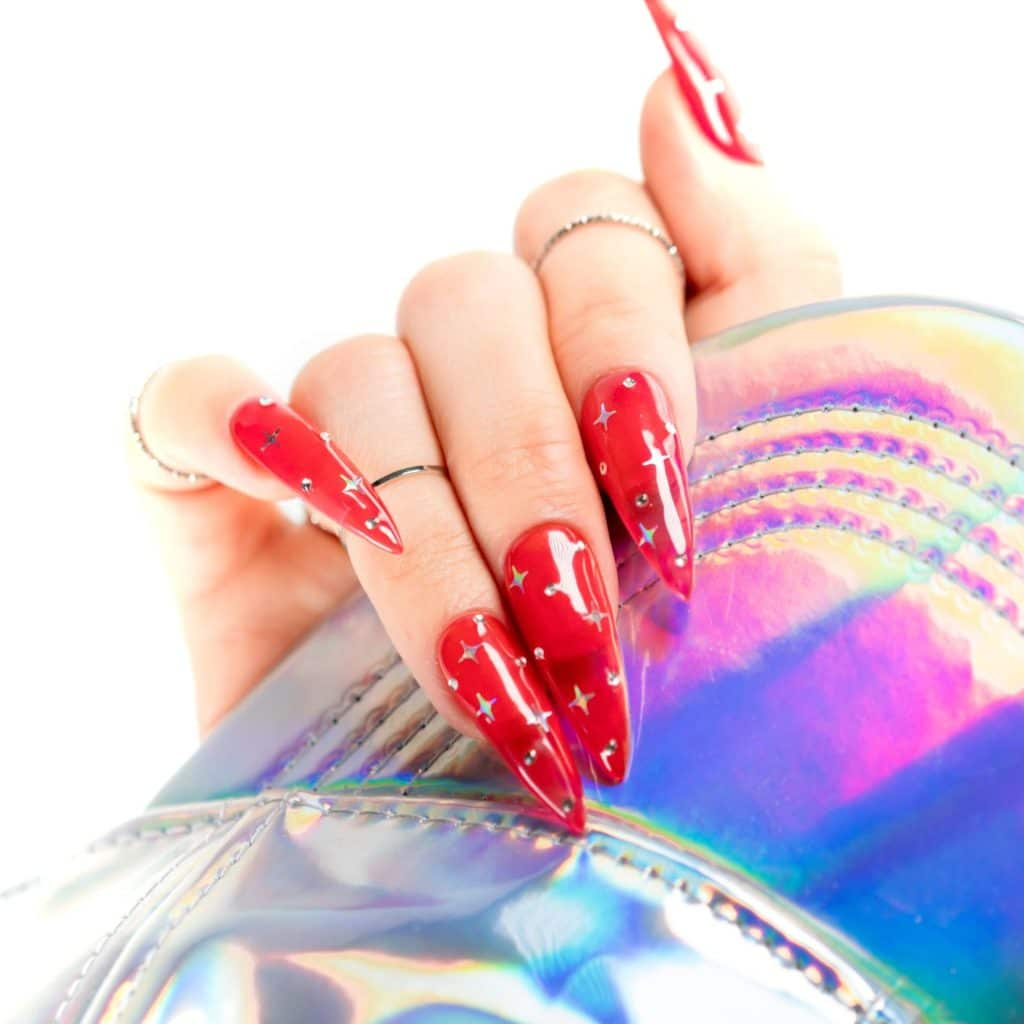 hand with bright translucent red nails clutching a colorful bag