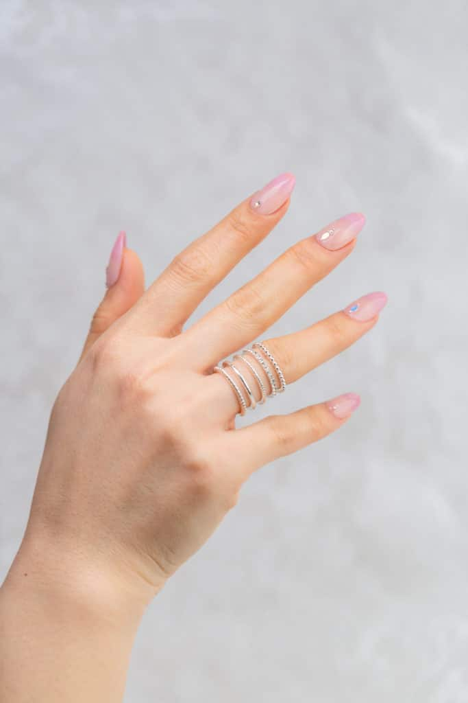 light pink ombre nails, rings on the hand, self care manicure