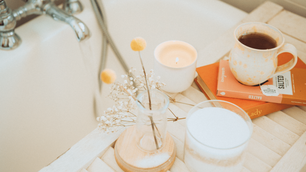 A serene self-care bath scene with soft white colors, a cup of tea, a candle, and a vase of flowers