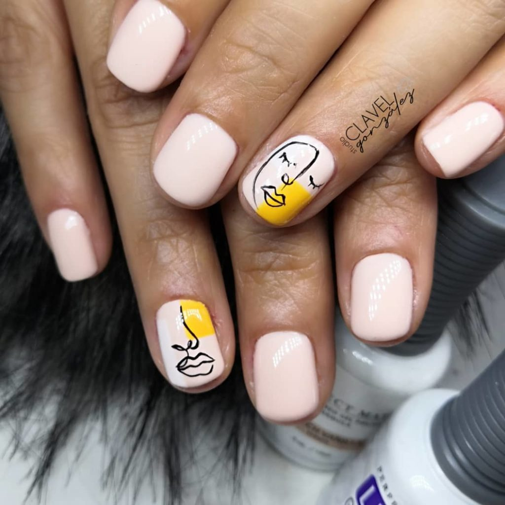 light nude color painted nails, two nails have abstract faces outlined in black and yellow