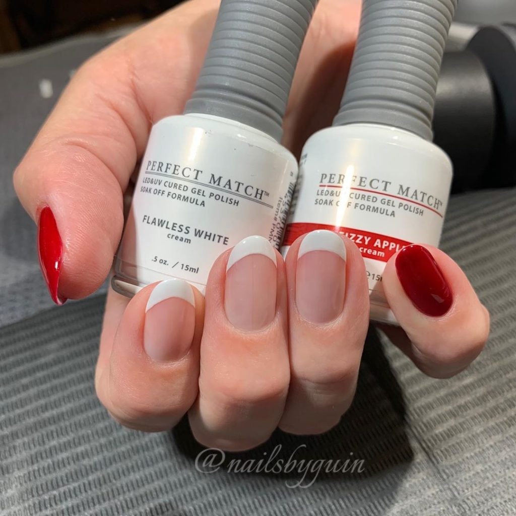 Hand holding two bottles of nail polish, middle three fingers painted with white french tip, pinky and thumb painted red, short nail designs