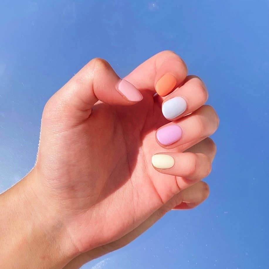 hand resting on a mirror, pastel gradient painted on the nails ranging from light pinks to orange. short nail designs