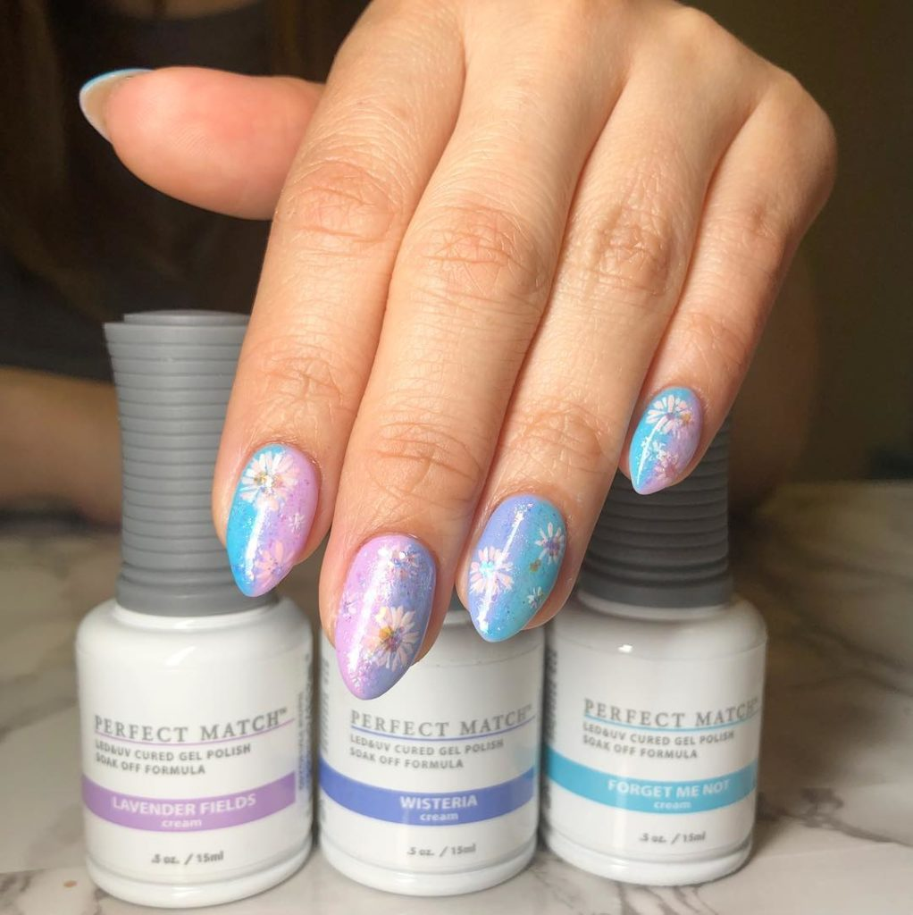 fingers painted with a pink, purple, and blue ombre design. with dried flowers in the nails. three nail polish bottles