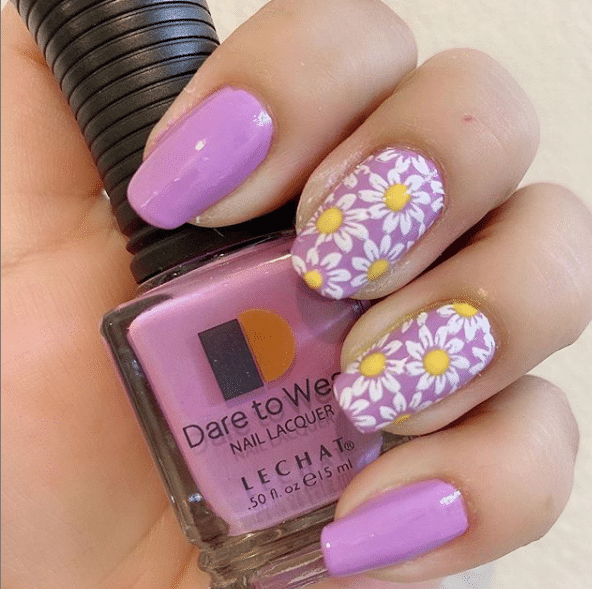 pink nails holding a nail polish bottle, two fingers have white daisies painted on them