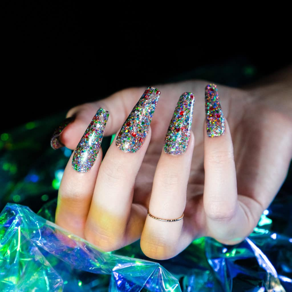 Hands showing off Solar Flare glitter gel nails