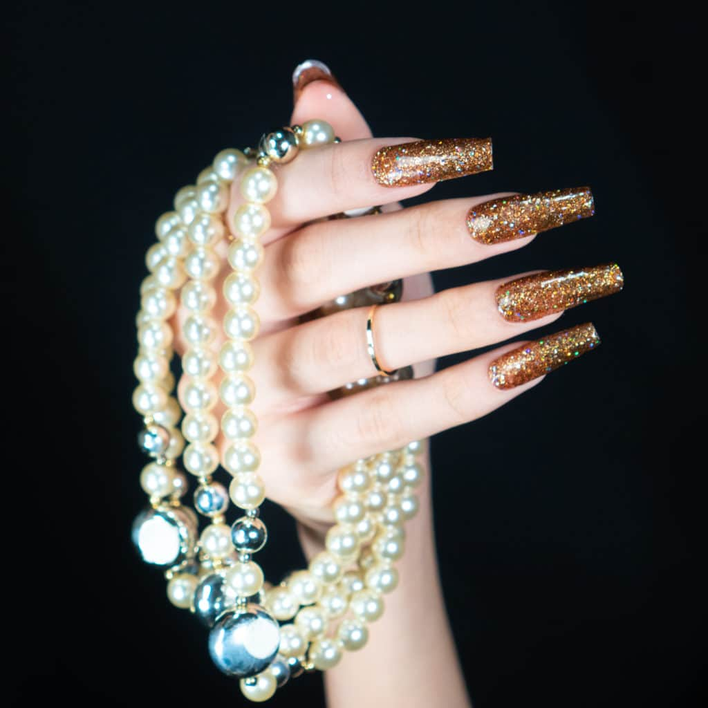 hand with a set of sparkly bronze nails holding a few pearl necklaces