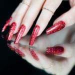 hand with a set of sparkly red nails